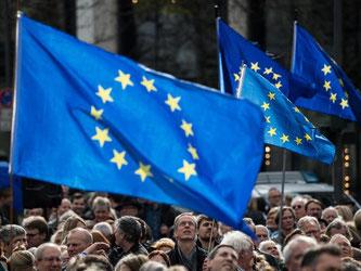 Kundgebungsteilnehmer schauen zu ihren Europaflaggen. Foto: Andreas Arnold/Archiv