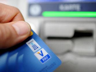 Ein Bankkunde hebt mit seiner Girokarte Bargeld von einem Geldautomaten ab. Foto: Angelika Warmuth/Illustration