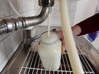 Eine Milchbäuerin zapft an ihrem Milchautomaten einen Liter Milch. Foto: Felix Kästle/Archiv
