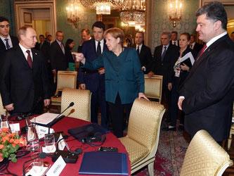 Krisentreffen in Mailand: Wladimir Putin (v.l.), Angela Merkel und Petro Poroschenko. Foto: Daniel Dal Zennaro