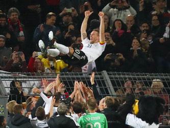 Lukas Podolski wurde nach dem Spiel von seinen Mannschaftskollegen groß gefeiert. Foto: Christian Charisius