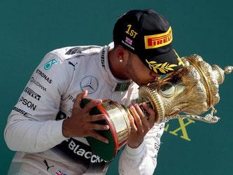 Lewis Hamilton küsst nach seinem Sieg die Silverstone-Trophäe. Foto: Geoff Caddick