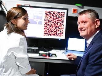 Gröhe (r) spricht im European Molecular Biology Laboratory mit Mitarbeiterin. Foto: Uwe Anspach/Archiv