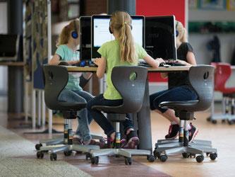 Schüler sitzen an einem Computer-Arbeitsplatz. Bundesbildungsministerin Wanka will Milliarden in die Ausstattung der Schulen mit Computern und freiem Internet stecken. Foto: Friso Gentsch/Symbol