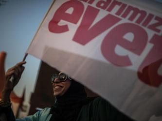 Eine Junge Frau hält in Istanbul eine Flagge mit dem türkischen Wort «evet» («ja») in der Hand. Die Türken entscheiden über eine Verfassungsänderung zur Einführung eines Präsidialsystems, das Staatspräsident Erdogan mehr Macht verleihen würde. Foto: Micha