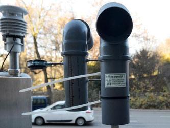 Hinter Messgeräten einer Feinstaubmessstation fahren Autos vorbei. Foto: Franziska Kraufmann/Archiv