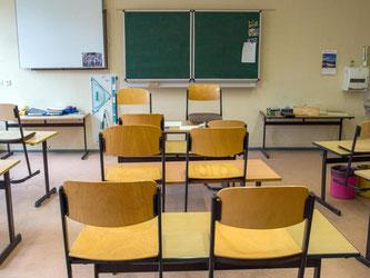 Blick in einen leeren Klassenraum, wo die Stühle auf den Bänken stehen. Foto: Patrick Pleul/Archiv
