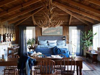 Rustikales Ambiente in modernen Zeiten: Zum Landhausstil gehört zum Beispiel auch die klassische Bettwäsche im holzlastigen Raum. Foto: Lexington