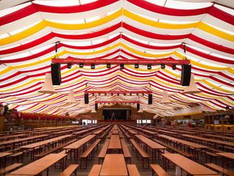 Leere Bierzeltgarnituren in einem großen Festzelt. Foto: Lino Mirgeler/Archiv
