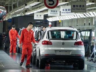 Mitarbeiter kontrollieren in einem VW-Werk in China einen Wagen. Foto: Ole Spata/Archiv
