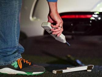 Ein Polizist misst den Lärmpegel am Auto eines mutmaßlichen Autoposer. Foto: Uwe Anspach