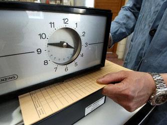 Eine Karte zur Arbeitszeiterfassung wird unter eine Stechuhr gelegt. Foto: Armin Weigel/Symbolbild