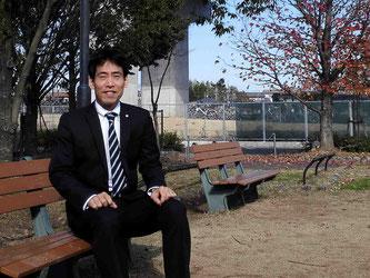 司法書士河合啓太が笑顔でベンチに座っている