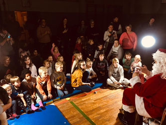 Weihnachtsmann vor Kinder.