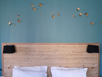 Détail, tête de lit en mélèze massif et papillons
