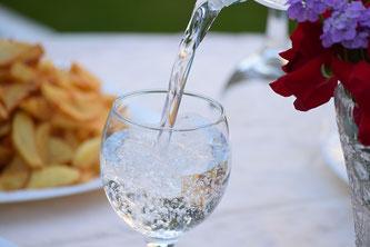 Ein Glas Mineralwasser wird zum Essen eingeschenkt
