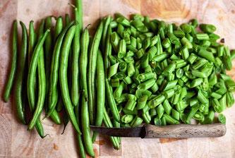 Grüne Bohnen auf Schneidbrett teilweise geschnitten