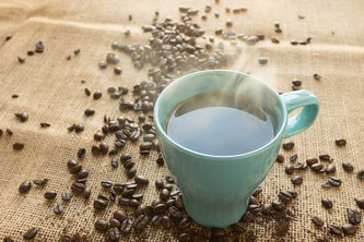 Tasse Kaffee neben Kaffeebohnen