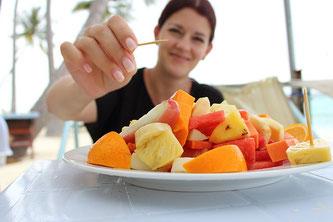Eine Frau isst Obstsalat mit einem Zahnstocher