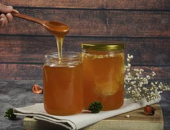 Honiggläser mit Löffel wird Honig geschöpft