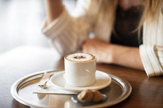 Frau sitzt vor einem Cappuccino