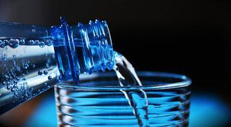Mineralwasser wird in ein Glas eingeschenkt
