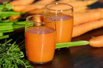 Karottensaft in Gläsern neben Karotten