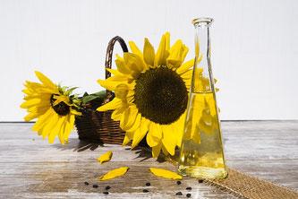 Blühende Sonnenblumen in einem Korb neben einer Flasche Öl