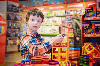 Kind spielt in Spielwarenhandlung