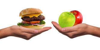 Hände mit Burger und Äpfel