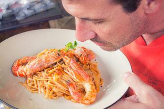 Mann riecht bei einem Teller Spaghetti mit Garnelen