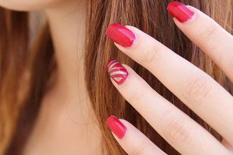 Frau mit rot lackierten Fingernägeln