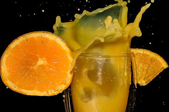 Orangensaft im Glas mit Orangen aufgeschnitten