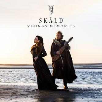 Zwei Musiker in altertümlicher Kleidung stehen am Strand und schauen in die Ferne.
