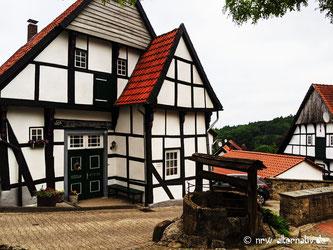 Ein Fachwerkhaus mit einem Brunnen davor in Tecklenburg-.