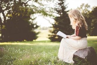 Hier sieht man eine Frau mit einem Buch auf einer Lichtung.