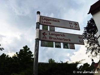 Ein rotes Fahrrad-Wegeschild, im Hintergrund Bäume.