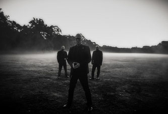Drei Musiker im Morgennebel. Das Bild ist Schwarzweiß und zeigt Covenant.