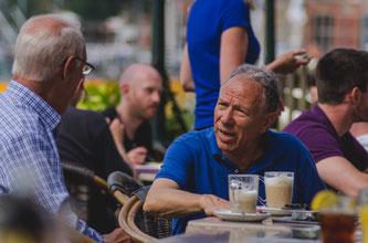 Zwei Männer sitzen draußen an einem Tisch mit Kaffee und unterhalten sich.