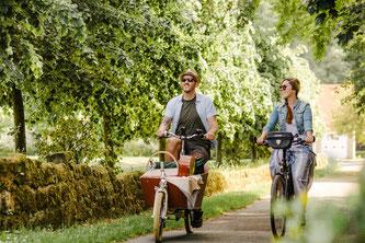 Zwei Menschen fahren auf Fahrrädern lächelnd durch eine Allee.