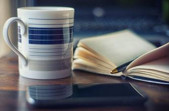 Becher Kaffee mit Notitzbuch und Händy