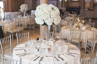 Cette photo représente une décoration de table de mariage avec un centre de table dans un vase martini et fleuri