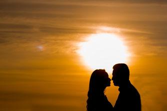 Sonnenaufgang von zwei liebenden glücklichen Menschen am Meer.