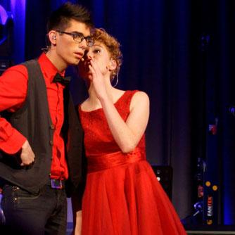 Ann-Kathrin flüstert Daniel etwas ins Ihr. Beide stehen auf einer großen Bühne in Abendkleidung.