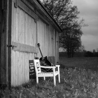 Eine Parkbank vor einer alten Holzhütte. Darauf eine Gitarre und eine Cajon.