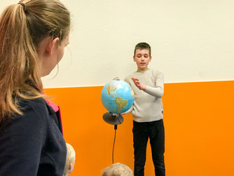 Auf einem Globus zeigt Dustin Bolle (Betreuer) den langen Transportweg von Mittelamerika nach Deutschland auf.