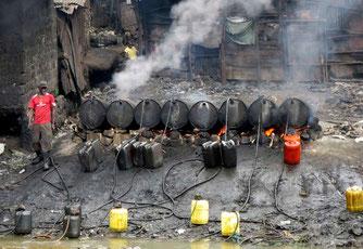 """Un lavoratore prepara un distillato alcolico tradizionale, conosciuto localmente come """"chang'aa"""", in una micro-fabbrica illegale di birra lungo il fiume nei sobborghi di Nairobi. 9 maggio 2014."""