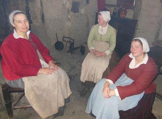 Three Women Huddled around a Smoky Fireplace Hearth