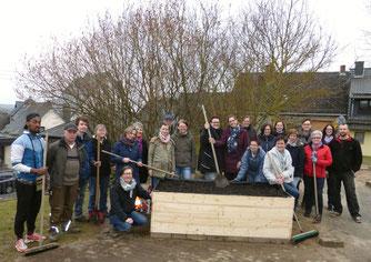 Workshop-TeilnehmerInnen vor dem fertig aufgestellten Hochbeet in der Kita St. Gangolf in Meudt