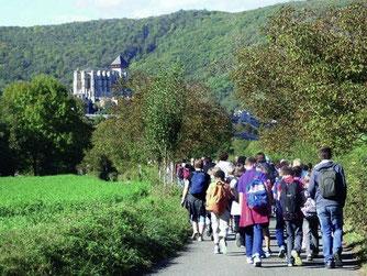 Cette image représente des élèves en randonnée vers la cité médiévale de Saint-Bertrand-de-Comminges, vue du côté de la basilique Saint-Just de Valcabrère.